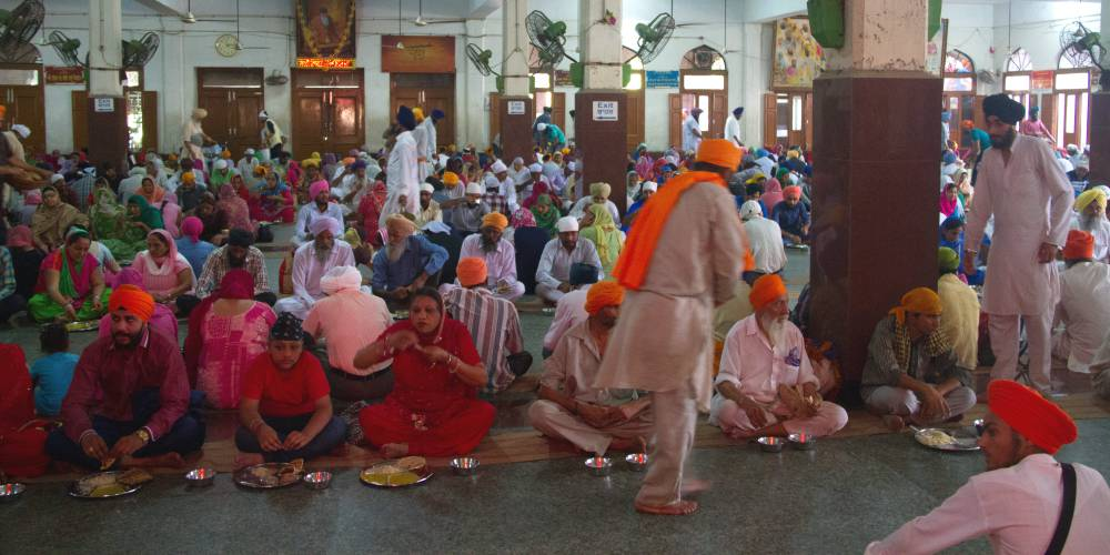 Langar hall and people eating in the Golden Temple, Amritsar, India