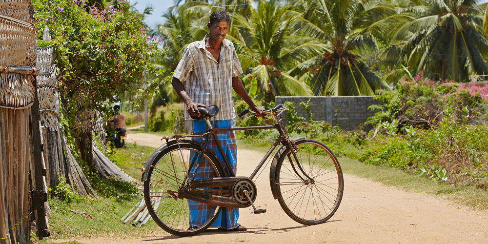 Man with old bicycle in rural village, Sri Lanka